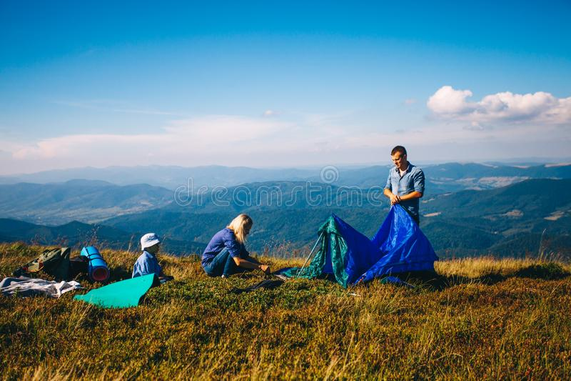 Родители и сын отдыхают возле отеля Tent On Camping Holiday стоковое фото