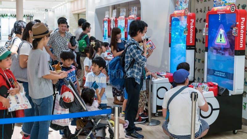 Родители с их детьми играя Pokemon клеймили видеоигры аркады в центре Pokemon, Токио, Японии стоковые фото