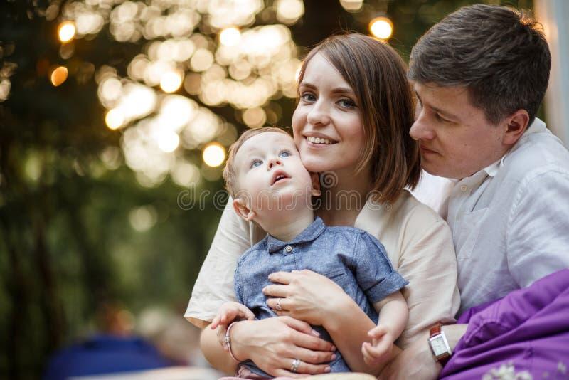 Родители с ребенком сидят в парке Ребенк смотрит вверх стоковые фотографии rf