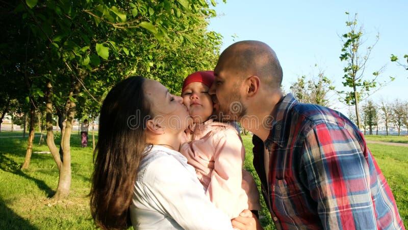Родители целуют ребенка на обеих щеках Счастливая молодая семья имея остатки на природе в парке на заходе солнца стоковое изображение