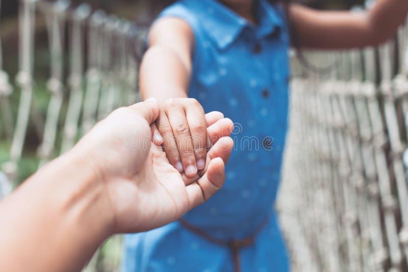 Родитель и ребенок держа руку совместно пока идущ стоковые изображения rf
