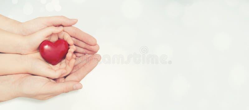 Родитель и ребенок держа сердце в руке стоковая фотография