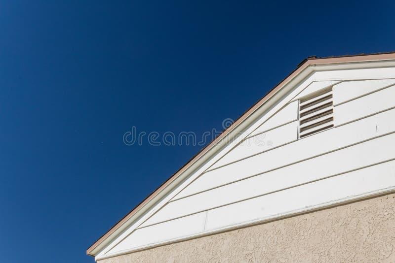 Родовой взгляд дома края стороны и крыши, штукатурки и винила с вентиляцией чердака установил против темносинего неба стоковое изображение