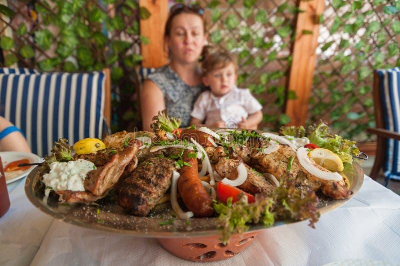 Родос, Греция 30-ое мая 2018 Плита Meze с традиционной местной едой на таблице в местном ресторане перед семьей Старый городок, стоковые фото