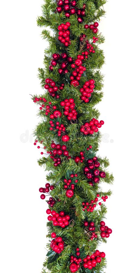 Рождественская Гарланд с красными ягодами, вертикально изолированная от белого стоковое фото