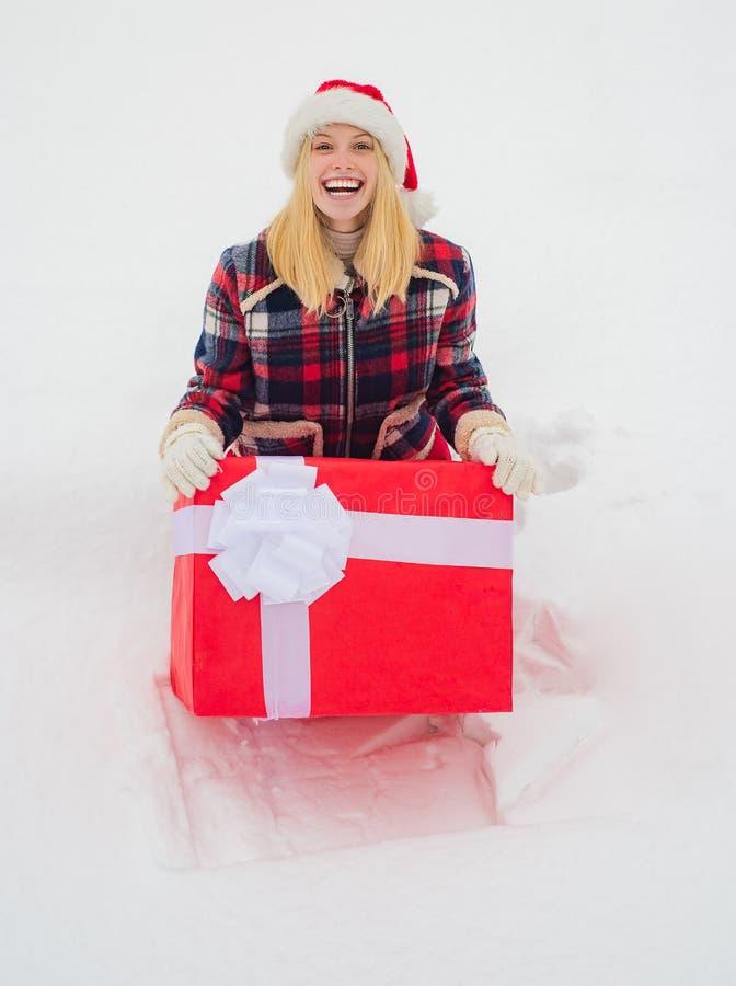 Рождественская девушка с большим подарком Счастливая женщина с настоящим или подарочным ящиком на улице Большой подарок Забавная  стоковые фотографии rf
