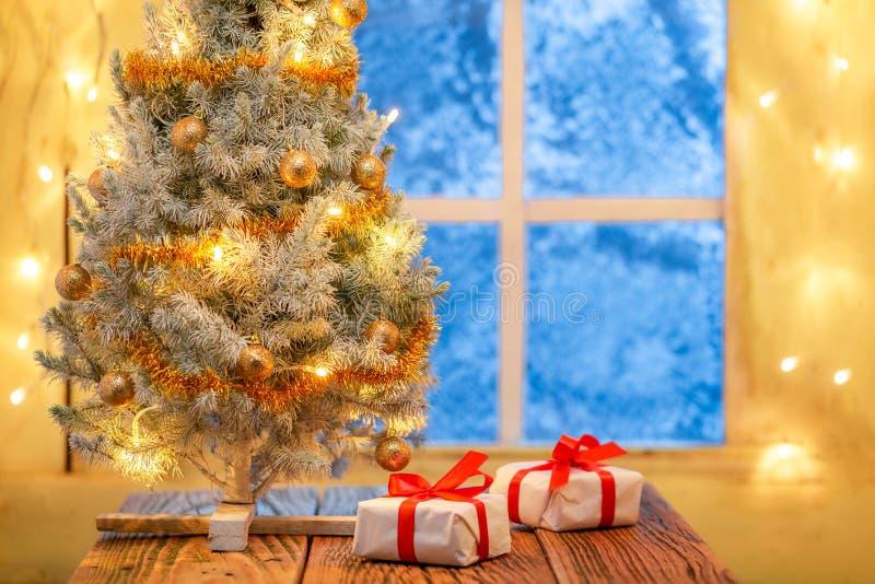 Рождественская елка и подарки золота с светами и замороженным окном стоковые изображения