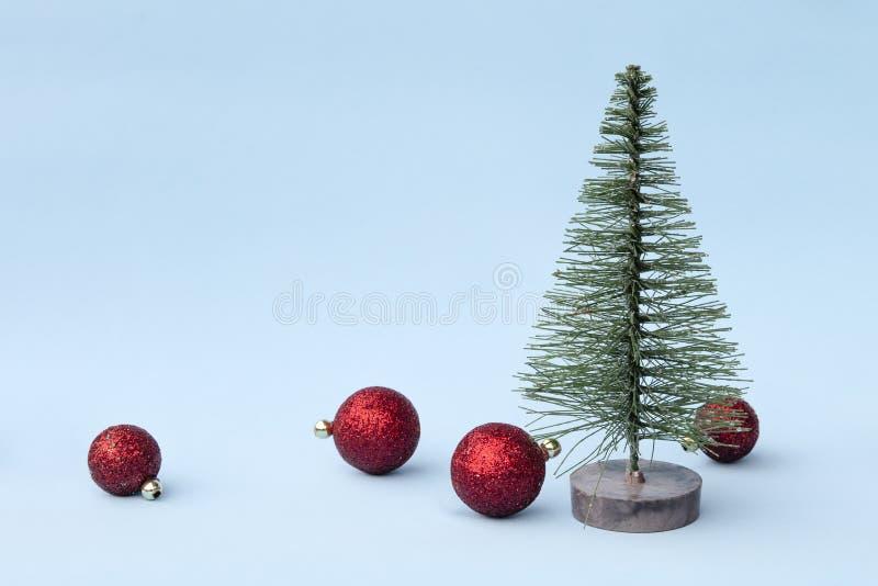 Рождественская елка, красные игрушки на голубой предпосылке в минимальном стиле Декоративные орнаменты рождества, Новый Год и кон стоковая фотография