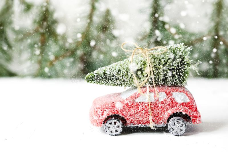 Рождественская елка на красной игрушке автомобиля с снегом Концепция зимнего отдыха стоковое изображение rf