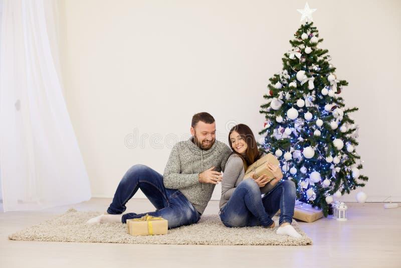 Рождественская елка подарков на рождество человека и женщины открытая с Новым Годом гирлянды стоковые изображения