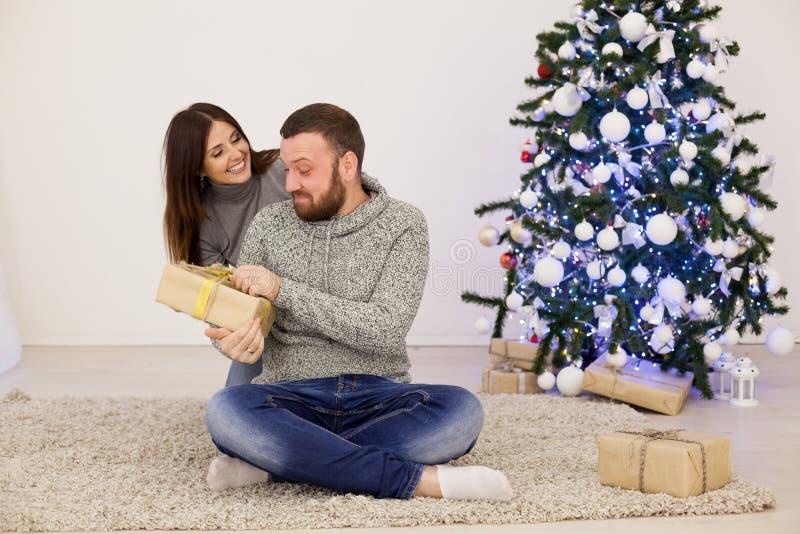 Рождественская елка подарков на рождество человека и женщины открытая с Новым Годом гирлянды стоковые фото