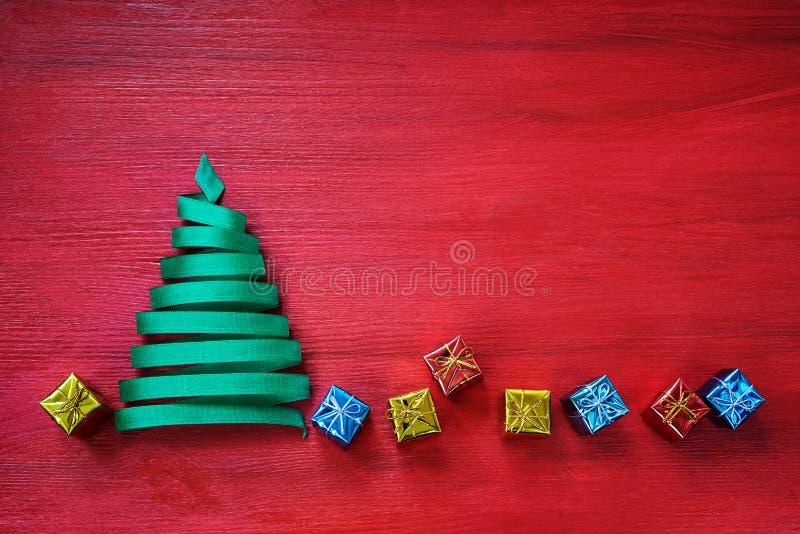 Рождественская елка сделанная от зеленой ленты с малыми подарками на красной предпосылке стоковые фотографии rf