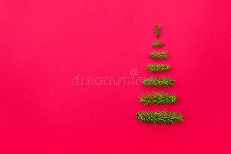Рождественская елка символа от ели разветвляет на красной предпосылке полисмен стоковое изображение