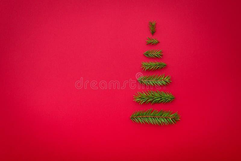 Рождественская елка символа от ели разветвляет на красной предпосылке полисмен стоковое фото