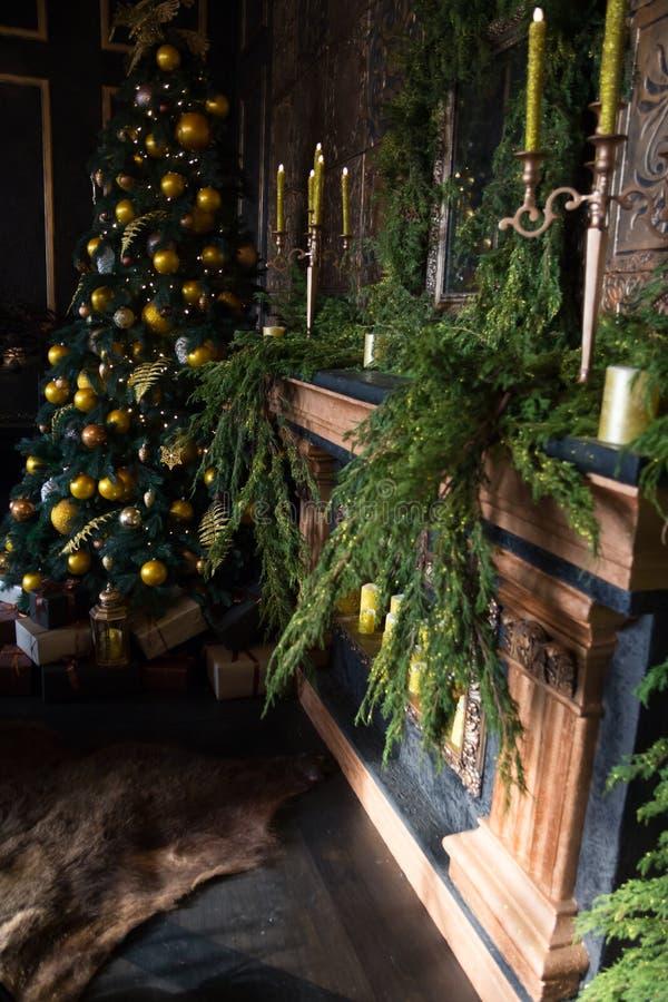 Рождественская елка с желтыми шариками, свечами и украшенным камином стоковые изображения