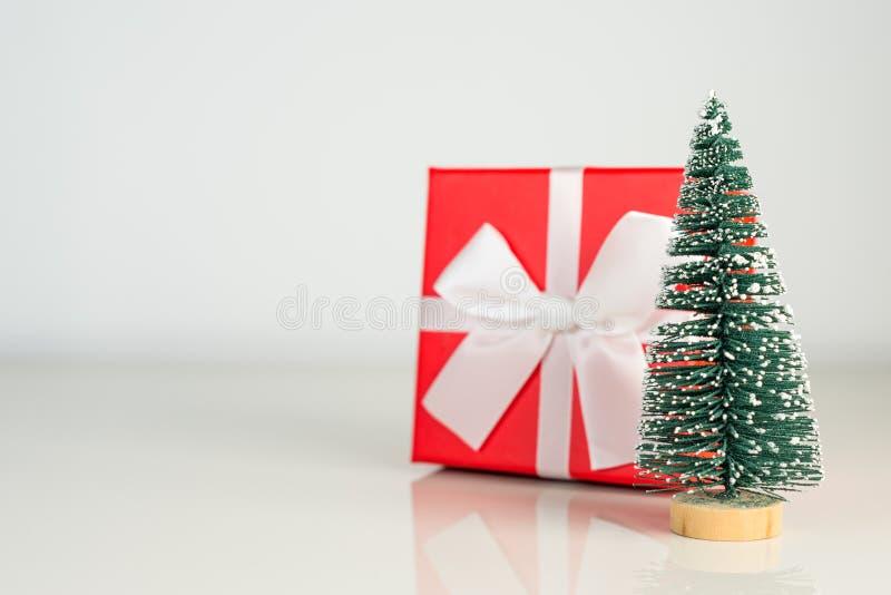 Рождественская елка с красной присутствующей коробкой на белой предпосылке, концепции праздников поздравительной открытки Рождест стоковые фотографии rf