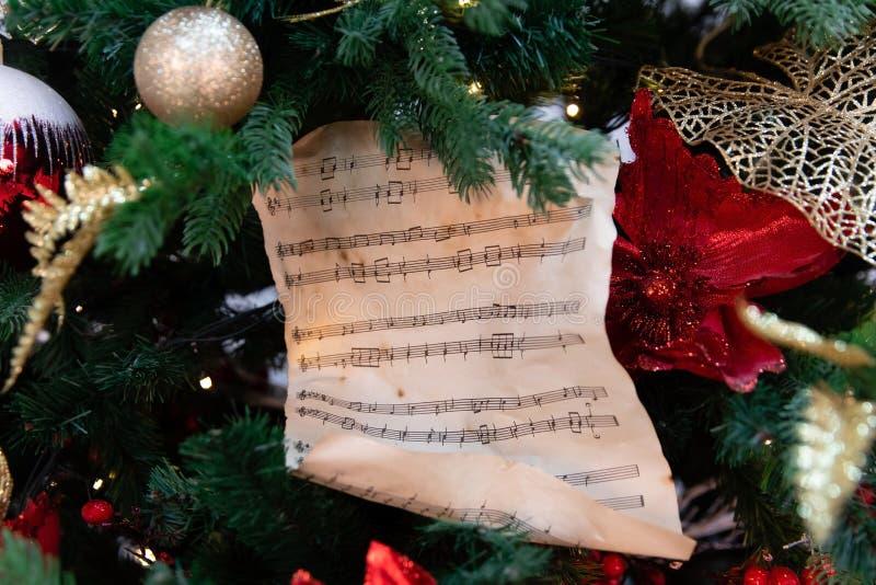 Рождественская елка украшенная с игрушками, светами и нотами стоковое фото