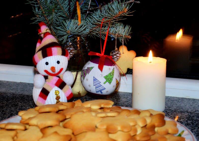 Рождественская елка украшенная с шариками, традиционно печенье пряника лежит на плите, рядом с ей стоит снеговик игрушки с сияющи стоковое изображение rf