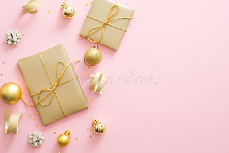 Рождественская композиция Рождественские золотые украшения, подарочные коробки, баубы, конфетти на пастельно-розовом фоне с копир стоковые изображения