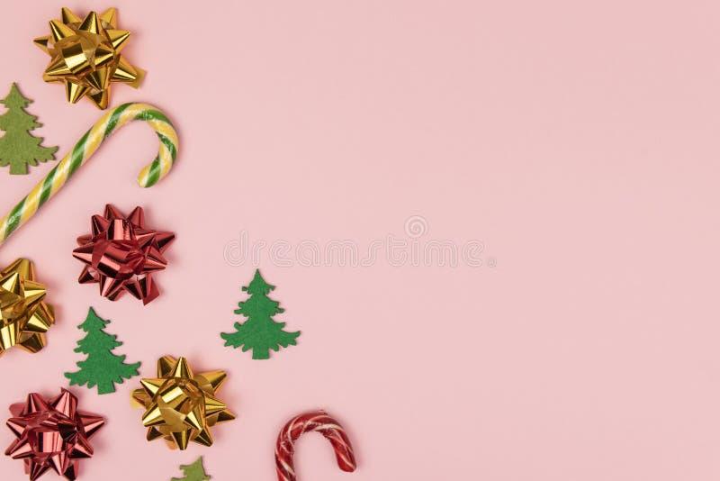 Рождественская композиция с луками, сладкими тростями и фруктовыми деревьями на пастельно-розовом фоне с копировальным пространст стоковая фотография rf