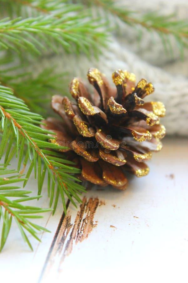 Рождественская открытка, конец - вверх конуса сосны покрытого с sequins золота, ветвями зеленого спруса на деревянной предпосылке стоковое фото rf