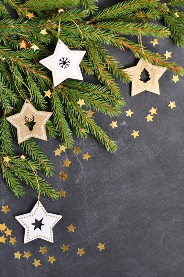 Рождественская открытка с ветвями ели, деревянное украшение звезды, confetti золота на темной предпосылке стоковое фото rf
