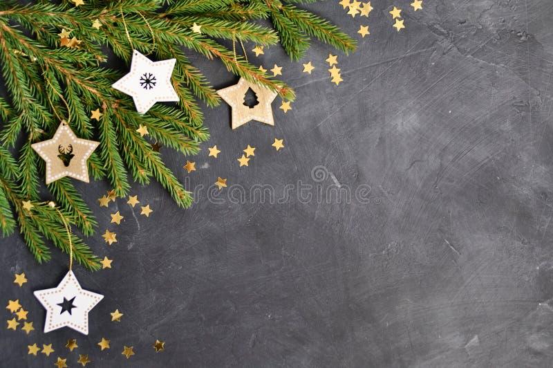 Рождественская открытка с ветвями ели, деревянное украшение звезды, confetti золота на темной предпосылке стоковые изображения rf