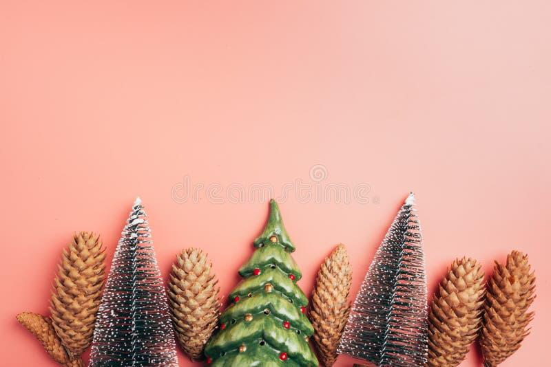 Рождественские елки и граница конусов сосны на розовой границе космоса экземпляра предпосылки стоковая фотография