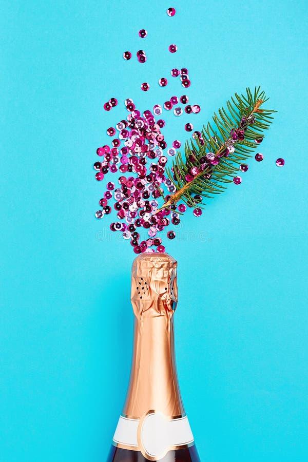 Рождественский и новогодний праздничный фон Бутылка шампанского и розовые искры на голубом фоне стоковая фотография rf