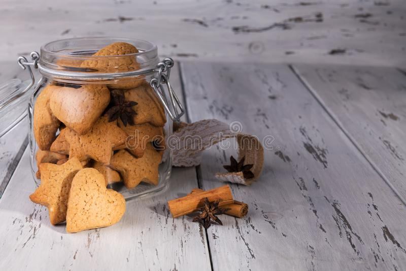 Рождественский съедобный подарок: имбиринтные печенья в форме печенья в виде сердечного печенья на обветшалом естественном деревя стоковое изображение