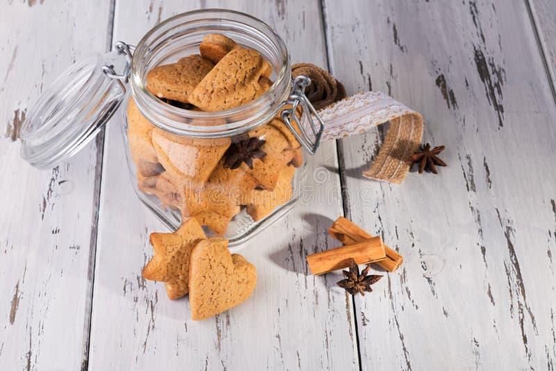 Рождественский съедобный подарок: имбиринтные печенья в форме печенья в виде сердечного печенья на обветшалом естественном деревя стоковое фото rf