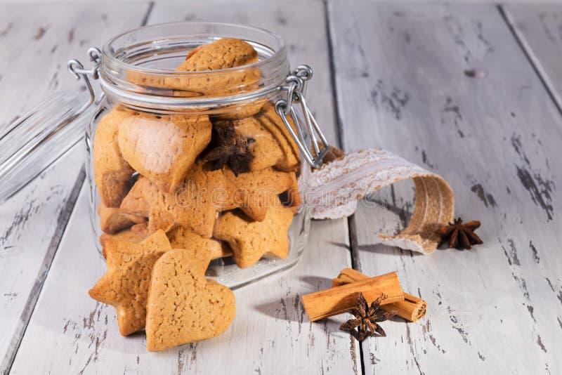 Рождественский съедобный подарок: имбиринтные печенья в форме печенья в виде сердечного печенья на обветшалом естественном деревя стоковое фото
