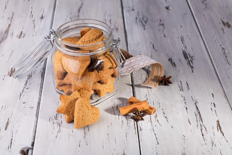 Рождественский съедобный подарок: имбиринтные печенья в форме печенья в виде сердечного печенья на обветшалом естественном деревя стоковые фото