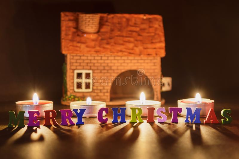 рождество веселое слово от пестротканых писем осветило свечами с домом глины на темной предпосылке Долгая выдержка стоковая фотография