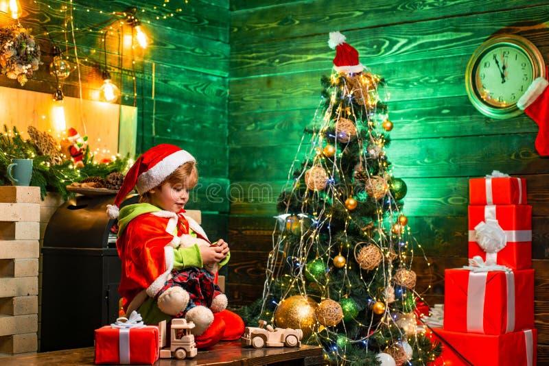 Рождество дня семьи Подарки и сюрпризы Милая игра мальчика маленького ребенка около рождественской елки E стоковые фото