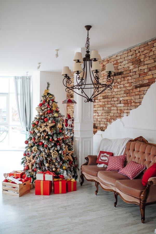 Рождество и Новый Год украсили внутреннюю комнату с красными настоящими моментами и деревом Нового Года и классическую коричневую стоковое фото