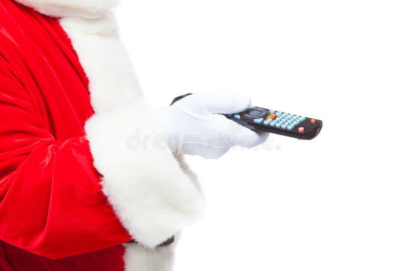 Рождество Конец-вверх Санта Клаус в белых перчатках держа дистанционное управление ТВ Просматривайте перечисления ТВ рождества, в стоковое фото