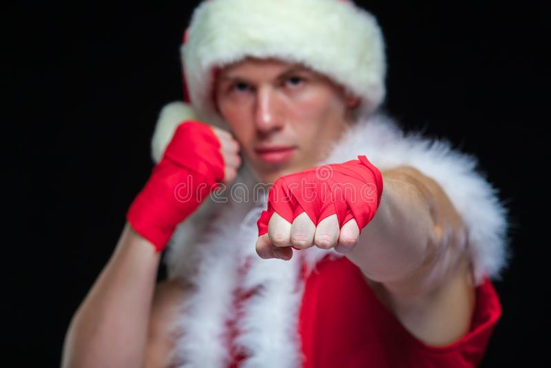 Рождество Мышечное kickbox бойца кладя Санта Клауса в коробку при красные повязки изолированные на черной предпосылке стоковое фото rf