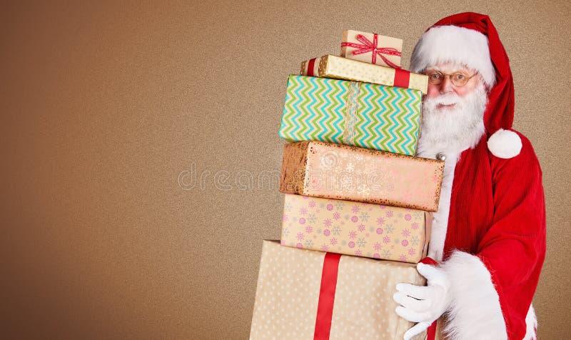 Рождество отца нося стог подарков против текстурированной коричневой предпосылки с космосом экземпляра для вашего приветствия пра стоковые фото