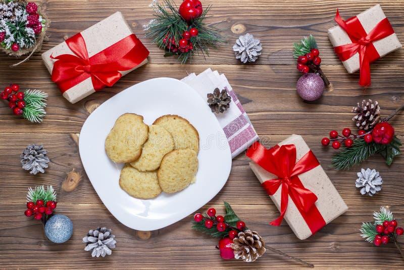 Рождество, предпосылка Нового Года открытки Плоск-положения, сверкная игрушки, печенья, конус над деревянным столом, взгляд сверх стоковая фотография rf