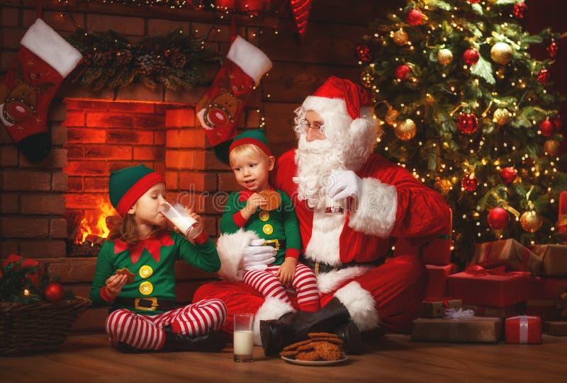 Рождество Санта Клаус с молоком питья эльфов и ест печенья стоковая фотография
