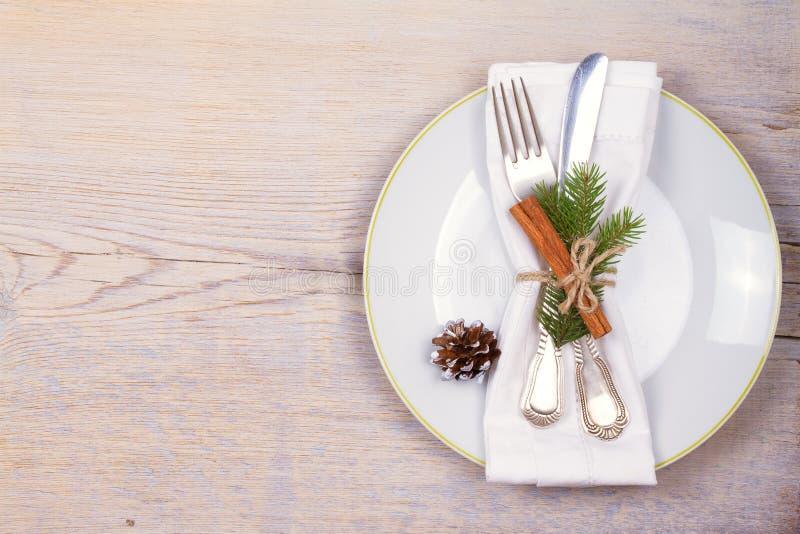 Рождество установило с плитой, столовым прибором, ветвями сосны, циннамоном и красными ягодами на деревянном месте Зимние отдыхи  стоковое фото