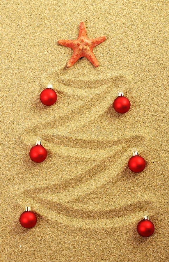 Рождественская елка на картине в песке с красными морскими звёздами и красными матовыми шариками рождества стоковое изображение rf