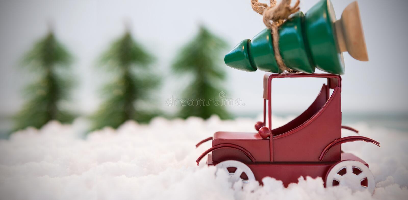Рождественская елка нося автомобиля игрушки на поддельном снеге стоковое изображение