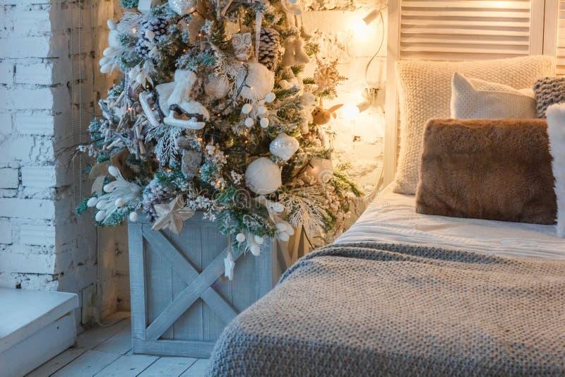 Рождественская елка около кровати в комнате стоковые фотографии rf
