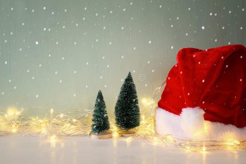 рождественская елка с светами гирлянды теплыми рядом с шляпой santa стоковая фотография rf
