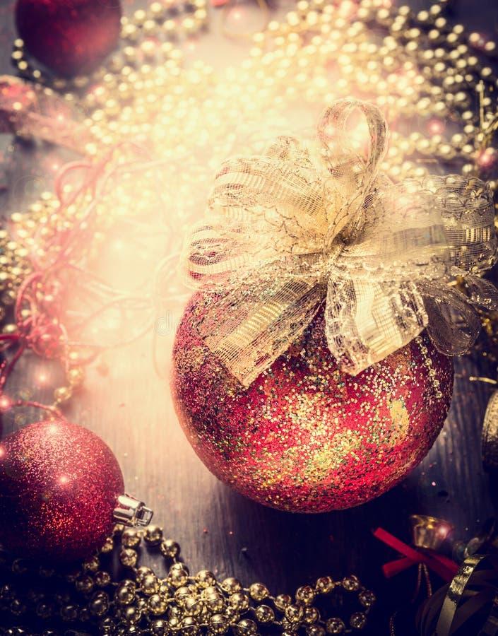 Рождественская открытка с красной винтажной безделушкой, золотой лентой и украшением на предпосылке праздника искры стоковые изображения