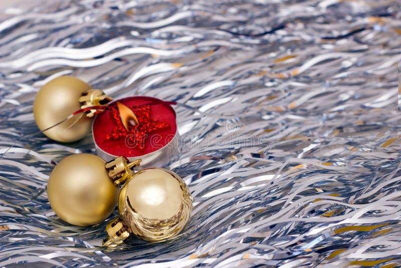 Рождество забавляется золотые шарики, горя красную свечу на серебряной предпосылке стоковые фото