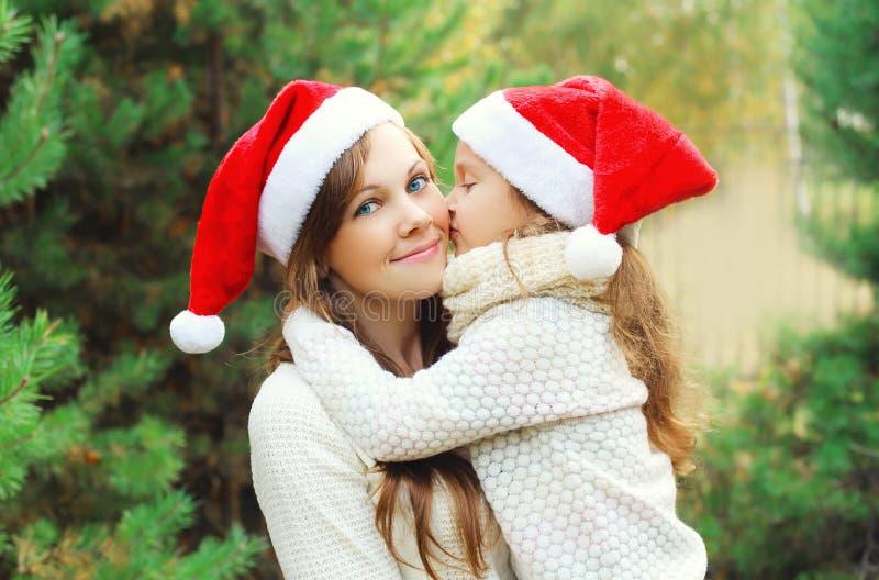 Рождество, концепция семьи - ребенок маленькой девочки целуя мать стоковое изображение