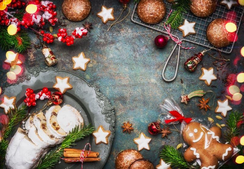 Рождество печь сладостную рамку еды с домодельным человеком пряника, печеньями, stollen с специями, ветвями ели и красным deco пр стоковое изображение